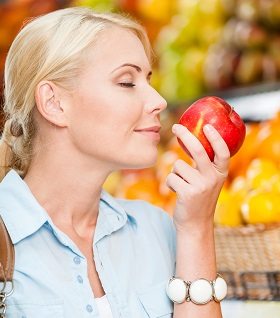 Girl at the shop choosing fruits and vegetables smells fresh red