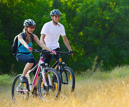 Young Happy Couple Riding Mountain Bikes Outdoor. Healthy Lifest
